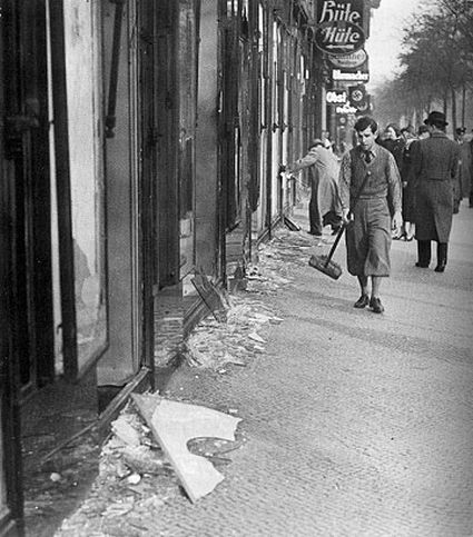A boy cleans the street after Kristallnacht.