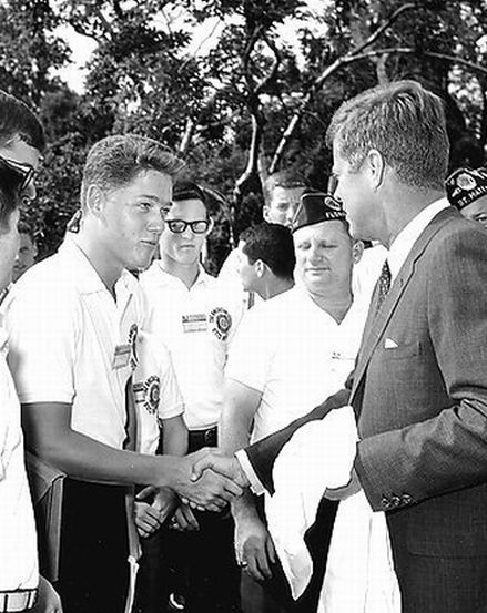 John Fitzgerald Kennedy shaking hands with teenager Bill Clinton.