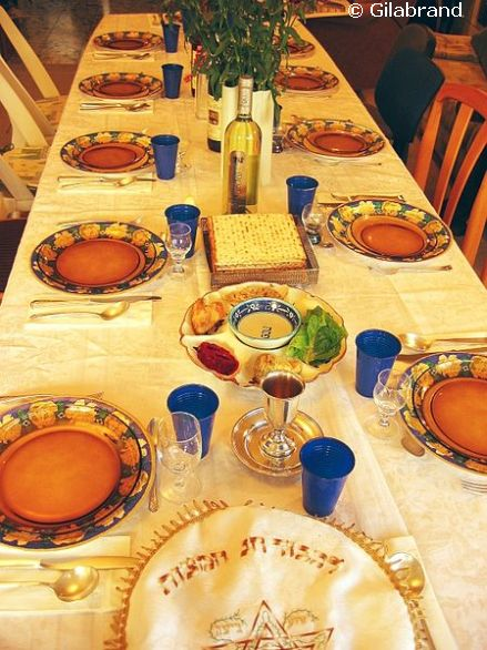 Festive Seder table with wine, matza and Seder plate.